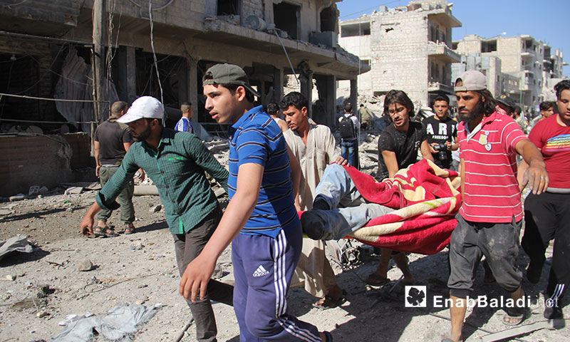 Volunteers of the Syria Civil Defense recovering civilians stuck beneath the rubble of houses, attacked by Russian aircraft in Ma`arat al-Nu`man, southern Idlib – July 22, 2019 (Enab Baladi)