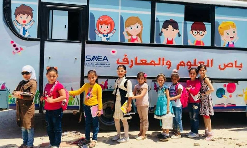 Children posing in front of al-Ma'aref/Knowledge Bus, rural Aleppo – July 25, 2019 (Qeeam Organization- Facebook)