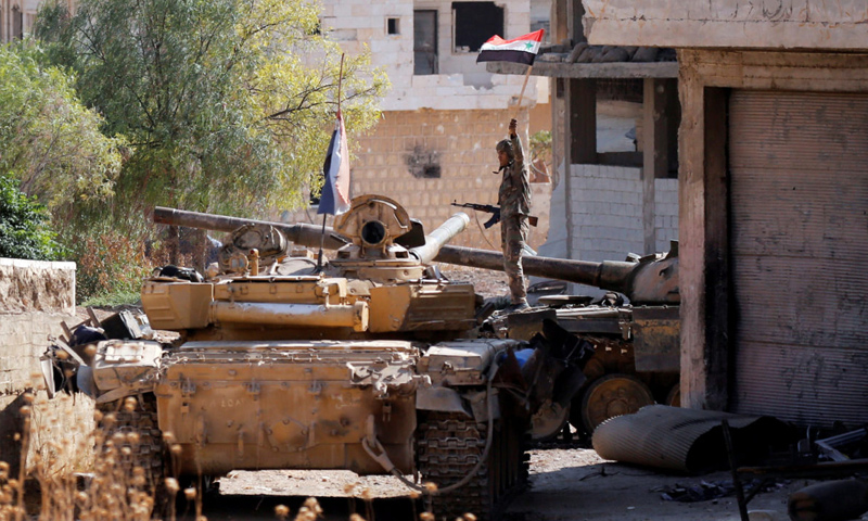 Soldier of the Syrian regime's forces carrying up the 'Syrian flag' aboard a tank in Khan Shaykhun, rural Idlib – August 30, 2019 (Reuters)