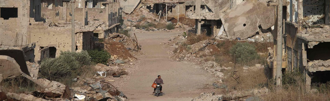 A man on his motorcycle behind him demolished buildings in southern city of Daraa - 2 August, 2018 (AFP)
