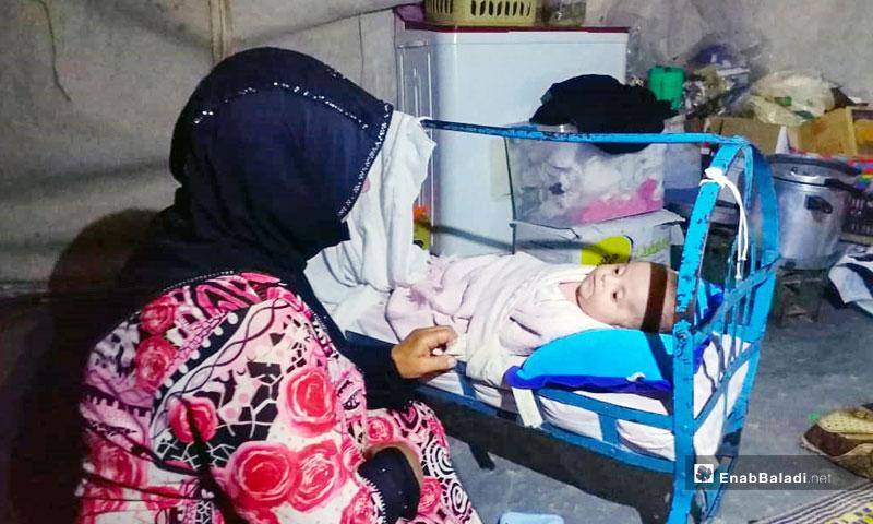 A mother beside her infant's crib in Camp al-Qala'a in Sarmada town, northern rural Idlib – August 11, 2019 (Enab Baladi)