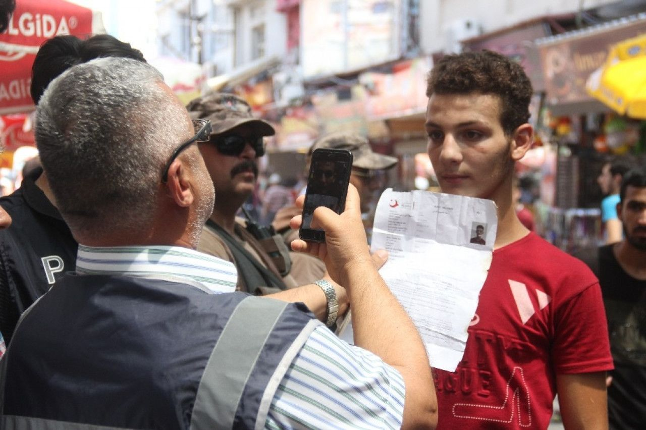 Turkish policeman taking a picture a Syrian refugee using his mobile phone in Adana - July 10, 2019 (Taraf Medya)