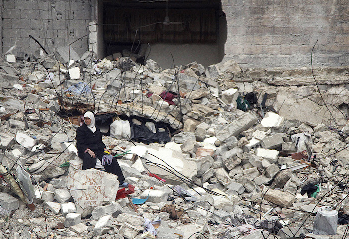 Syrian woman sitting among the rubble of houses destroyed by Syrian missiles (pappaspost)