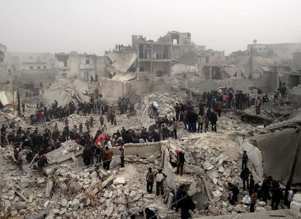 Syrians inspecting destruction following a missile attack on Aleppo in February 2013 (AFP)