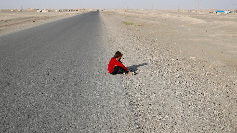 A child sitting on the edge of a road at al-Karamah village in Raqqa - 2017 (Reuters)
