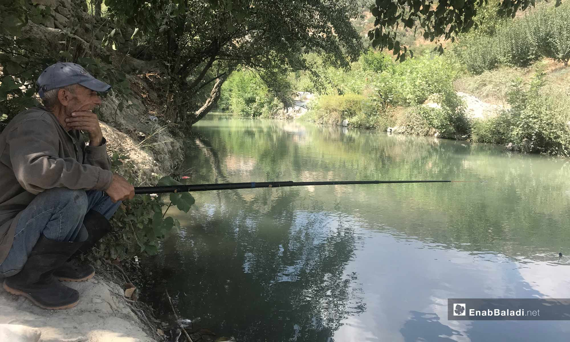 A man fishing in the Assi River, near the city of Darkoush, western rural Idlib -September 8, 2019 (Enab Baladi)