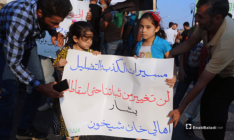 """Demonstration held at the Clock Square in Idlib city, demanding the liberation of Khan Shaykhun and offsetting the Syrian regime. The sign carried by the protestors says: """"The demonstrations of lies and defamation would not waver our steadfastness until Bashar is overthrown"""" – September 16, 2019 (Enab Baladi)"""