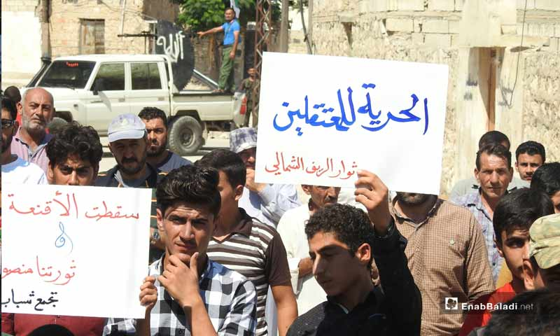 """Demonstrations in the towns of Dabiq, Binnish and  Kafar Takharim, rural Aleppo, on the Friday of """"Together We Are Brought by the Revolution and United by Its Flag We Stand"""". The sign the protestor is carrying says: """"Freedom for detainees"""" – September 13, 2019 (Enab Baladi)"""