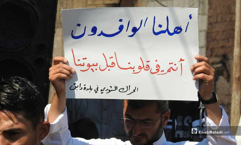 """Demonstrations in the towns of Dabiq, Binnish and  Kafar Takharim, rural Aleppo, on the Friday of """"Together We Are Brought by the Revolution and United by Its Flag We Stand"""". The protestor in the phot carrying a sign that say: """"Our people, newly displaced, you reside in our hearts before our houses"""" – September 13, 2019 (Enab Baladi)"""