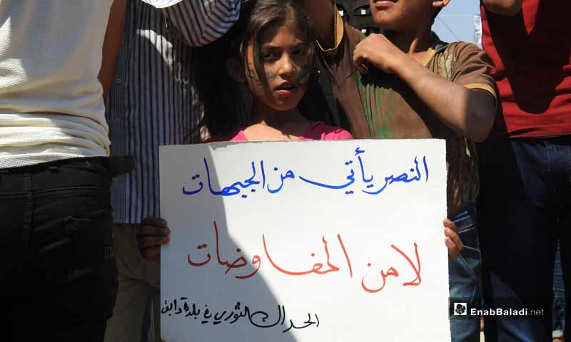 """Demonstrations in the towns of Dabiq, Binnish and  Kafar Takharim, rural Aleppo, on the Friday of """"Together We Are Brought by the Revolution and United by Its Flag We Stand"""". The sign carried by the little girl says: """"It is not negotiations that bring victory; it is the battlefronts""""– September 13, 2019 (Enab Baladi)"""