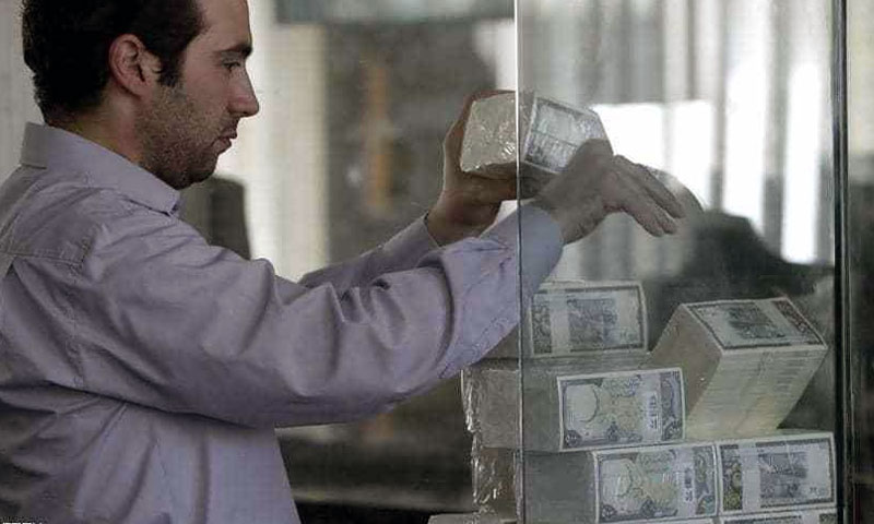 Syrian Central Bank employee arranging 500-Pound money bills - (AFP)