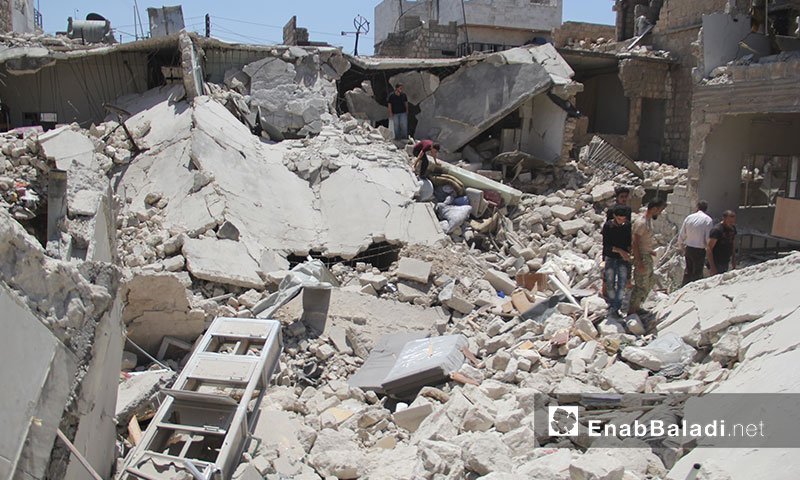 Members of Civil Defence lifting civilians trapped under the rubble of homes, destroyed during a Russian airstrike on Maarat al-Numan, south of Idlib - July 22, 2019(Enab Baladi)