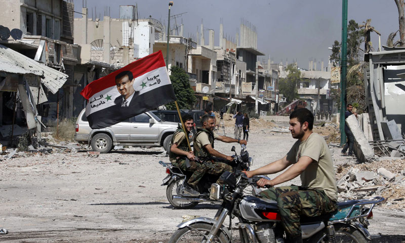 Militants of the Syrian regime holding a flag, on which the face of Bashar al-Assad is printed, in the city of al-Qusayr, Homs, after they controlled it – June 7, 2019 (Reuters)