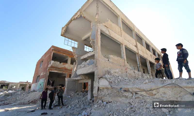 Children looking at their school, destroyed as a result ofbombardment in the city of Binnish - 27 September 2019 (Enab Baladi)
