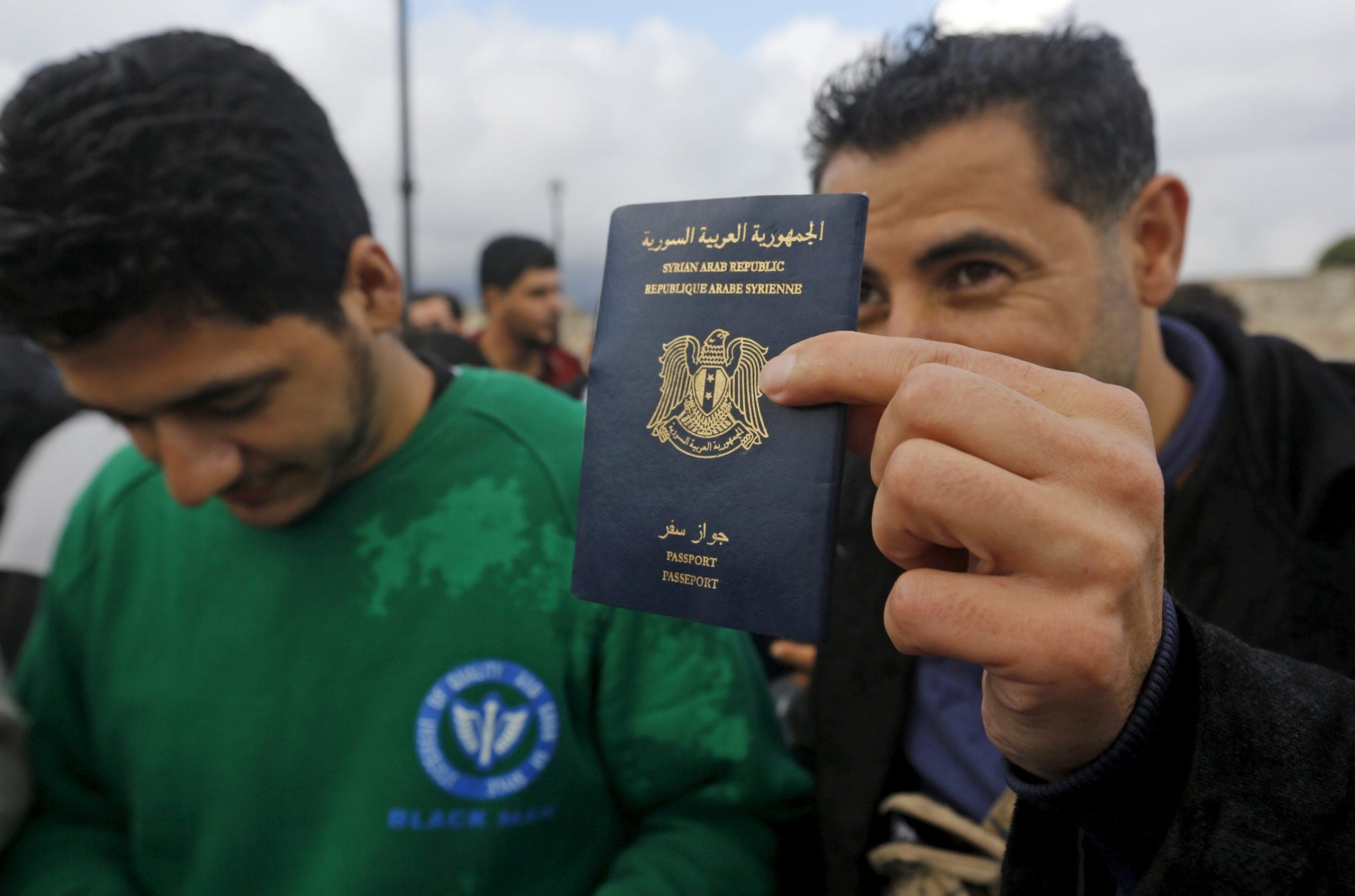 Syrian refugee showing his passport after being rescued by a Greek Coast Guard patrol boat – May 29, 2015 (Reuters)