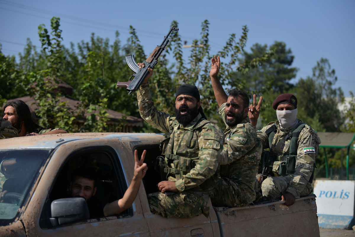 Elements of Turkey-backed NationalArmy ride on a military truck near the town of Tel Abyad - 11 October 2019 (Reuters)