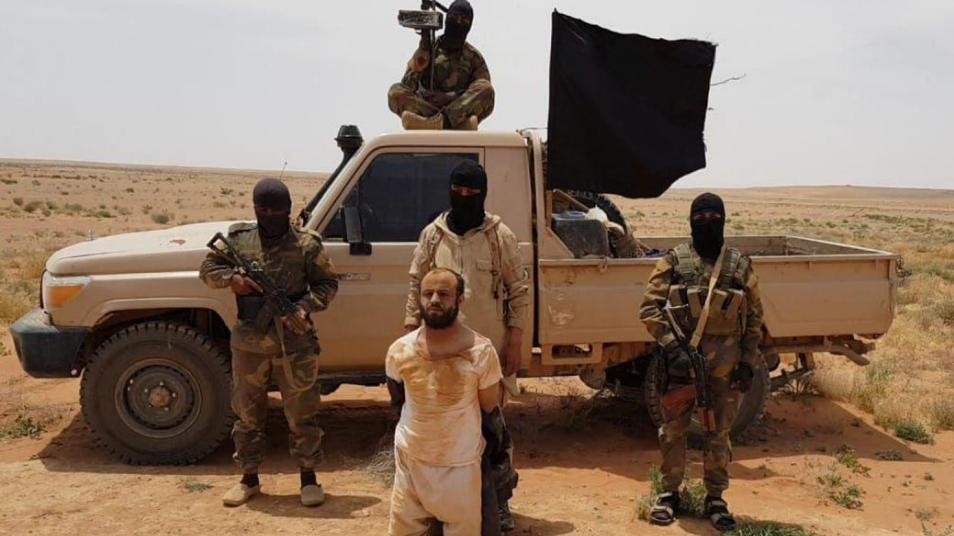 ISIS fighters behind a captive in the Syrian desert