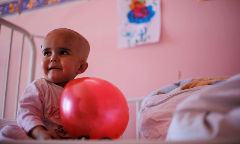 A child plays with a balloon inside a cancer treatment department at the Children's Hospital in Syria –February 20, 2017 (Reuters)