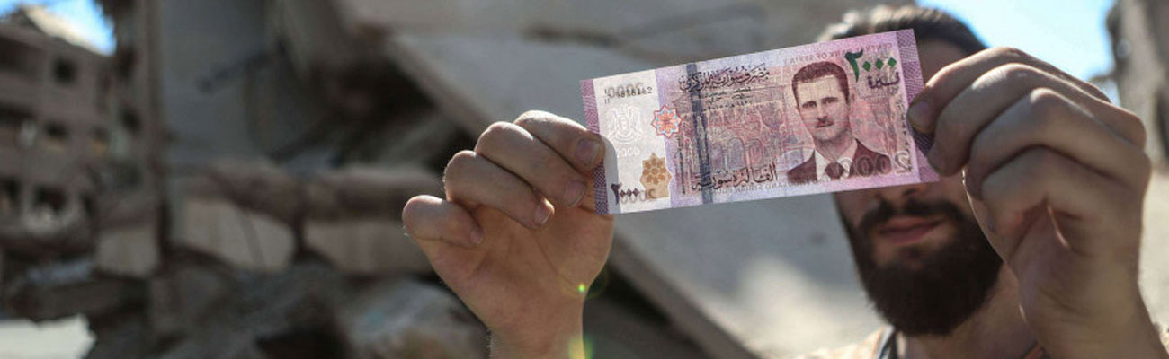 A Syrian man carrying a 2,000 Syrian pounds banknote. (shutterstock)