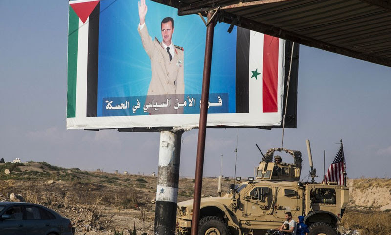 American armored vehicle in front of a photo of head of the Syrian regime, Bashar al-Assad, Qamishli Northern Syria, 26 November 2019
