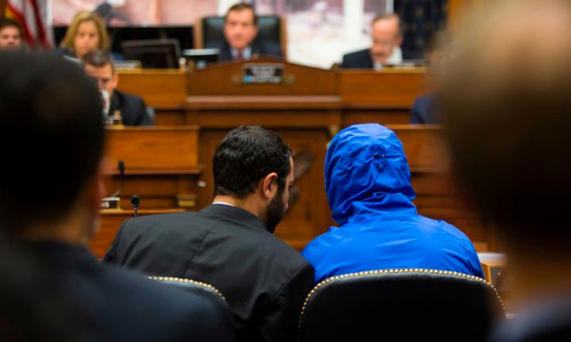 Syrian defector Caesar conceals his identity as he listens with a translator to the House Foreign Affairs Committee in 2014 (CNN)