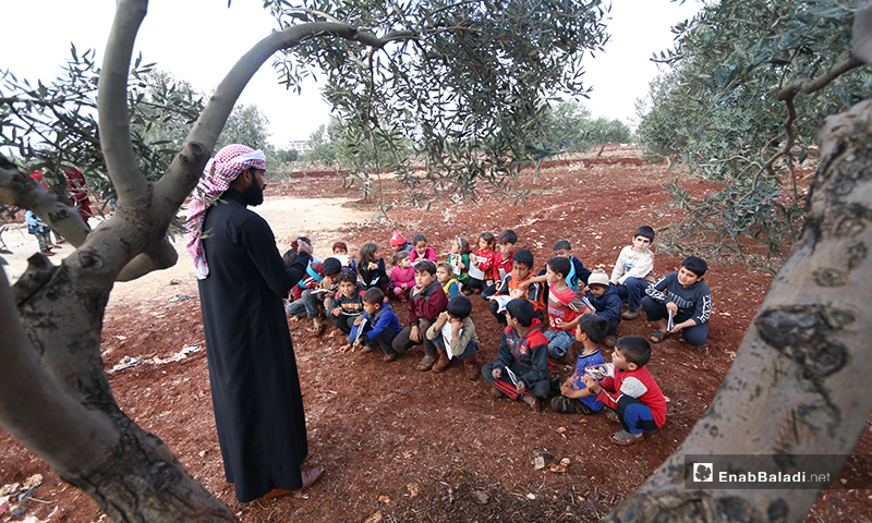 A wall-less school under olive trees in Senjar refugee camp in the northern countryside of Idlib –3 December 2019 (Enab Baladi)