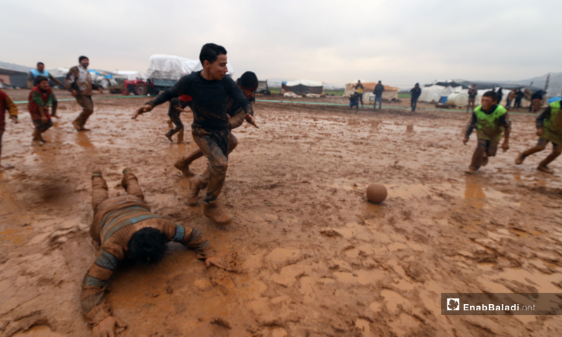 Children play football on the muddy ground at an IDP camp near the town of Sarmada in the province of Idlib - 2 January 2020 (Enab Baladi)