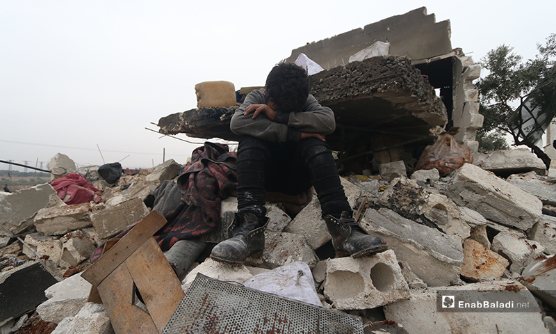 A child sits on the rubble of what was once his home in the town of Kafr Taal, in the western countryside of Aleppo - 20 January 2020 (Enab Baladi)