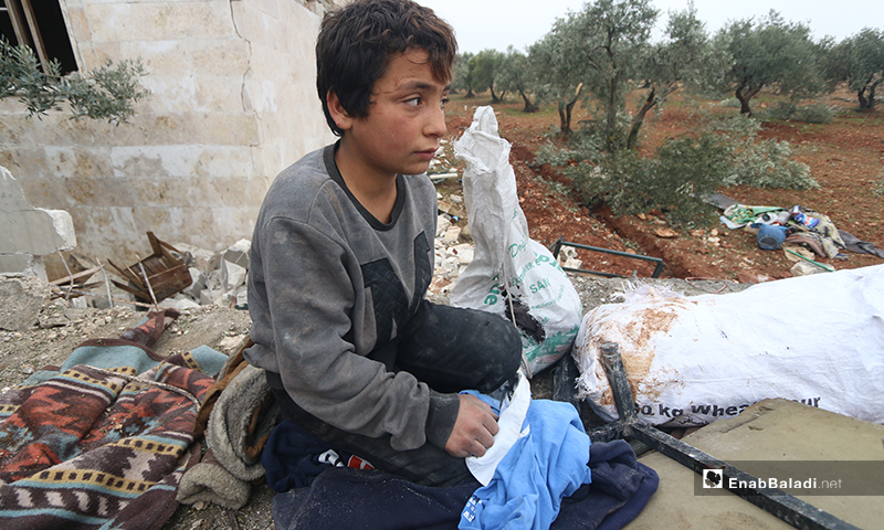 A child scavenges what he can from the debris of his home in the town of Kafr Taal in the western countryside of Aleppo - 20 January 2020 (Enab Baladi)