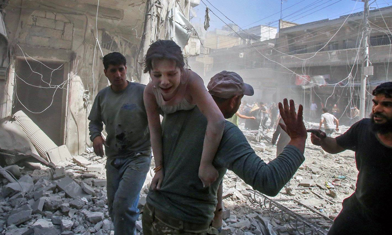 A man rescuing a child after an airstrike by military aircraft in Maarat al-Numan, in southern countryside of Idlib, on 26 May, 2019 (AFP)