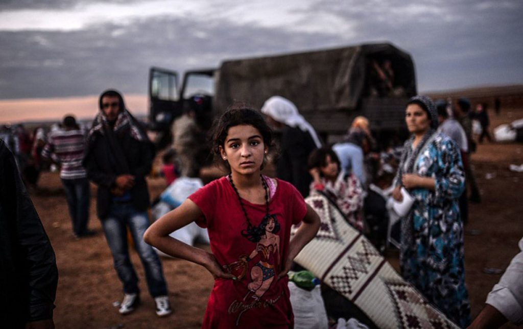 Syrian-Kurdish girl crossing borders into Turkey (AFP)