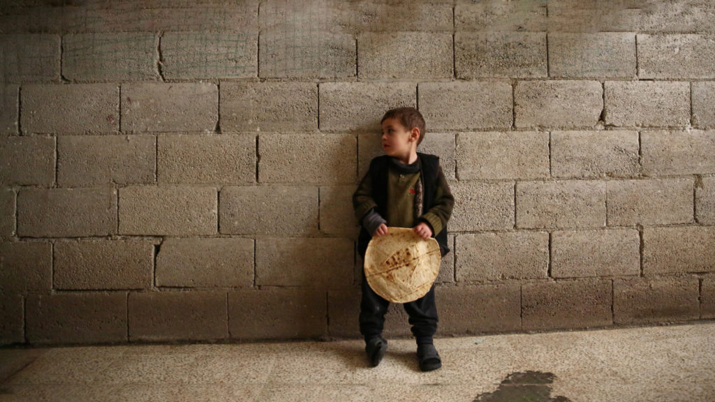 Syrian child holding a loaf of bread (AFP)