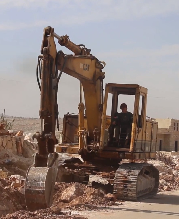 A machine of the local council of the city of Hass during the road maintenance operations in the town - 2018 (Enab Baladi)