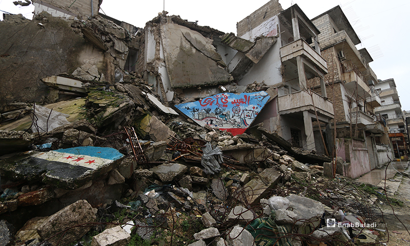 A mural in the rubbles of houses demolished by the Russian and Syrian regime forces' bombardment on  the town of Ariha, south of Idlib - 8 February 2020 (Enab Baladi)