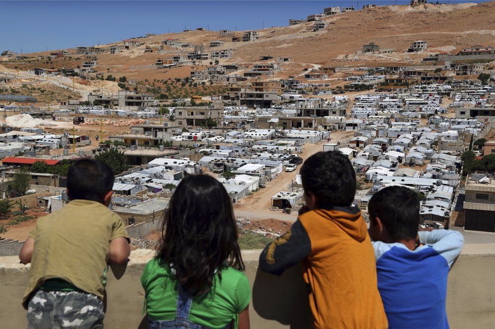 Lebanese children looking from the roof of their house at the Syrian refugee camps in Aarsal - 16 June 2019 (AP)