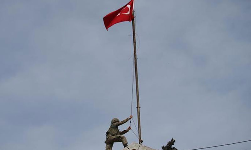 A Turkish soldier raises his country's flag in the city of Afrin in northern Syria (Anadolu)