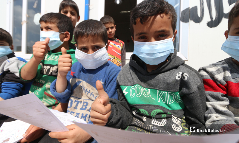 """Children putting on face masks during an activity to promote awareness of the dangers of the """"Coronavirus"""" in Atmeh camps - 16 March 2020 (Enab Baladi)"""