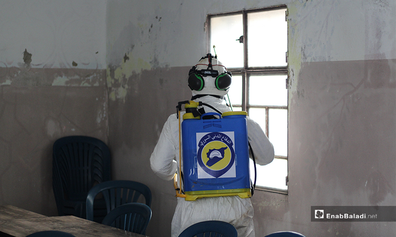 A member of the Syria Civil Defense team while disinfecting a Scholl's window in Dabiq town of northern rural Aleppo – 29 March 2020 (Enab Baladi)