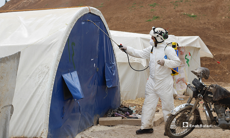 A member of Syria Civil Defense team spraying disinfectants on the entrance of a tent in the IDPs' camp of Dabiq town in northern rural Aleppo – 29 March 2020 (Enab Baladi)