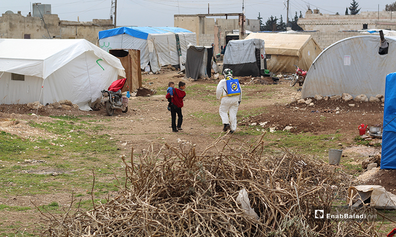 A member of Syria Civil Defense team and an internally displaced Syrian child in Dabiq town's IDPs' camp of northern rural Aleppo – 29 March 2020 (Enab Baladi)