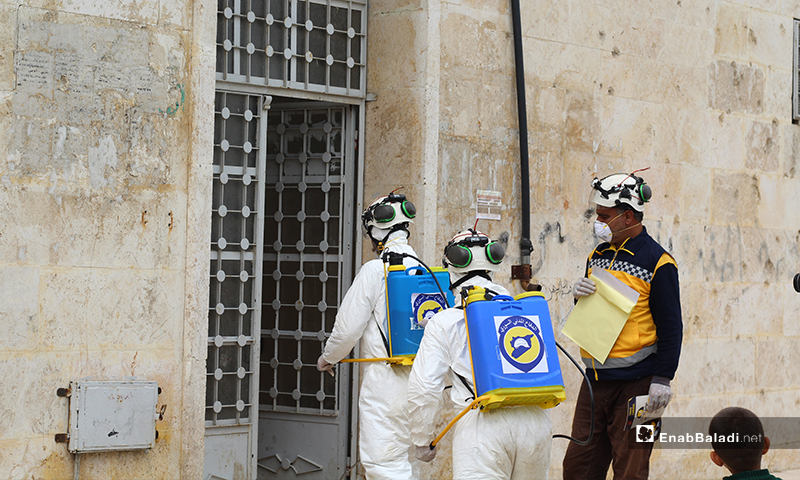Syria Civil Defense voluntary teems while disinfecting one of the mosques'  gates in Dabiq town of northern rural Aleppo – 29 March 2020 (Enab Baladi)