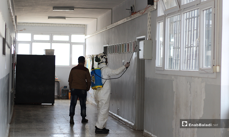 One of the Syria Civil Defense team members while disinfecting a school hallway in Dabiq town of northern rural Aleppo – 29 March 2020 (Enab Baladi)
