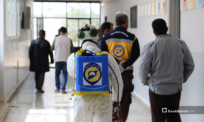 Members of Syria Civil Defense team while walking through the hallways of one of the schools of Dabiq town in northern rural Aleppo as part of the disinfecting campaign against the novel coronavirus (Covid-19) – 29 March 2020 (Enab Baladi)