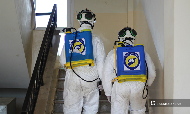 Two members of the Syria Civil Defense team while disinfecting the stairs of a school in Dabiq town of northern rural Aleppo against the novel coronavirus (Covid-19) – 29 March 2020 (Enab Baladi)