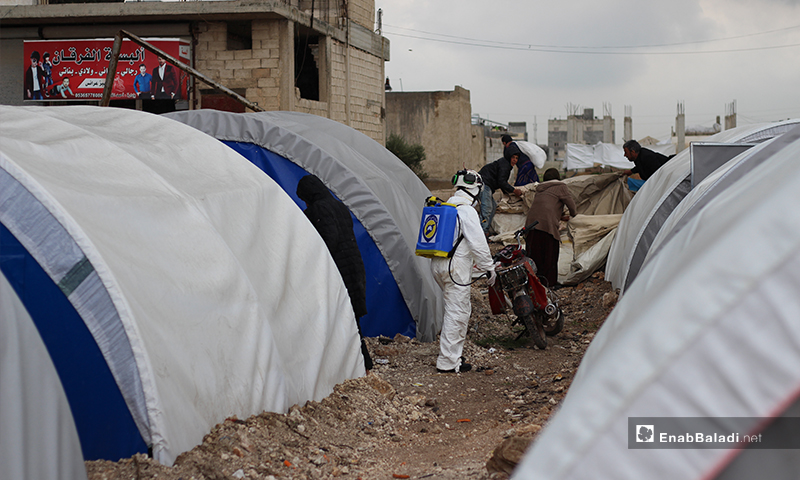 A member of the Syria Civil Defense team disinfecting between the tents of IDPs in Dabiq town of northern rural Aleppo – 29 March 2020 (Enab Baladi)
