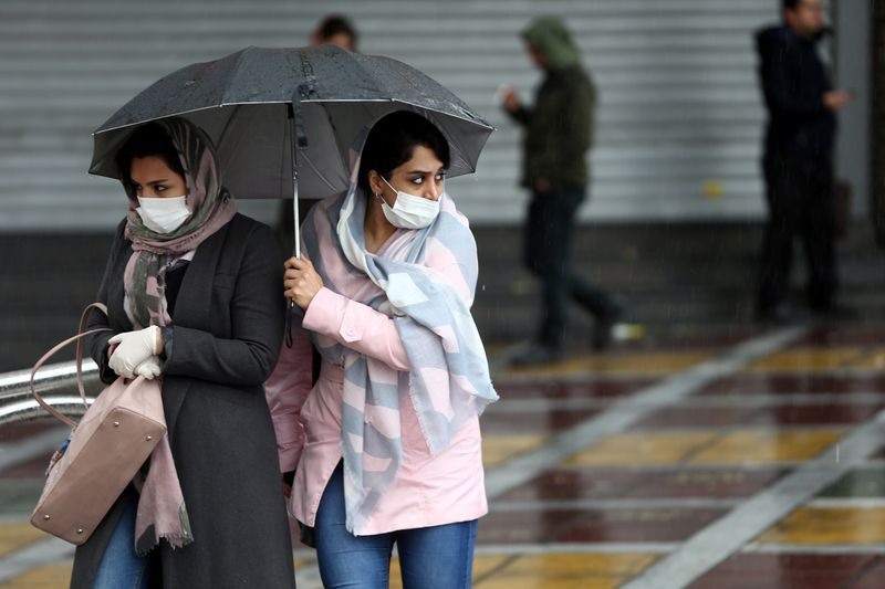 Two women wearing protection masks from the new Coronavirus in a street in Tehran - 25 February 2020 - (Reuters)