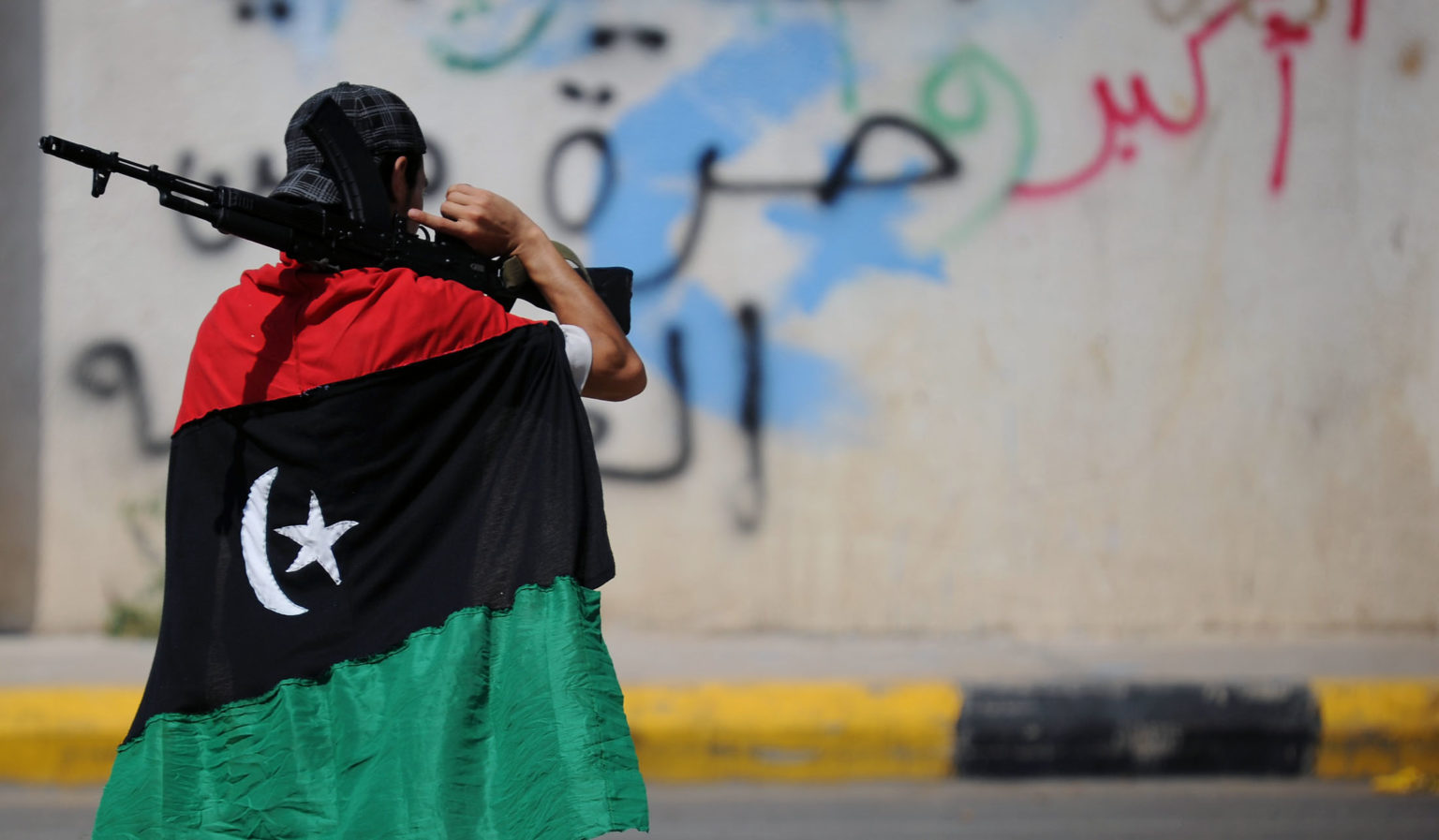 Libyan fighter covered with the Libyan flag carries a gun– 17 February 2019 (ERM network)