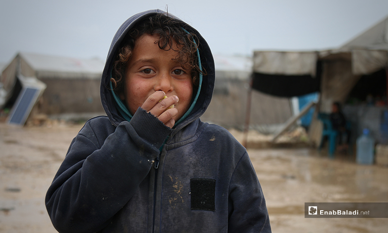 A child from Aleppo Labeeh camp, eating under the rain – 24 April 2020 (Enab Baladi)