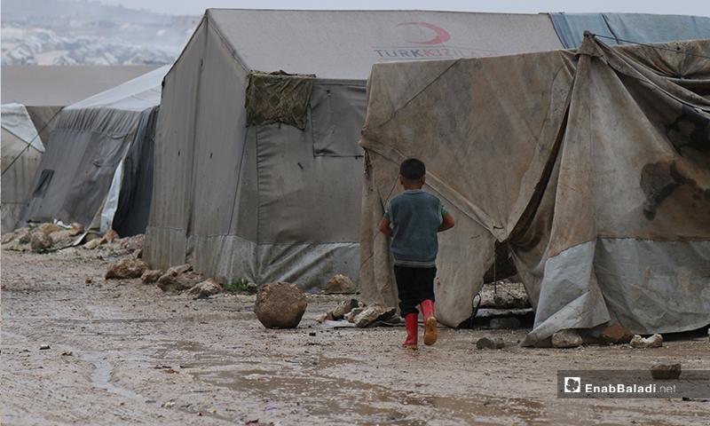 A child walking on the rainwater gathered in Aleppo Labeeh camp – 24 April 2020 (Enab Baladi)