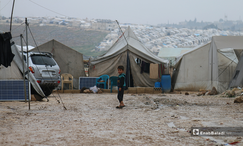 A child standing in front of IDPs tents in Aleppo Labeeh camp, during the first day of Ramadan – 24 April 2020 (Enab Baladi)